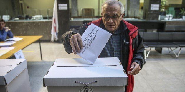 ZAGREB, CROATIA - NOVEMBER 08: A Croatian man casts his ballot for the parliamentary elections at a polling...