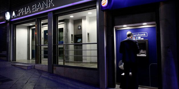 A customer uses an automated teller machines (ATM) operated by Eurobank Ergasias SA beside an Alpha Bank...