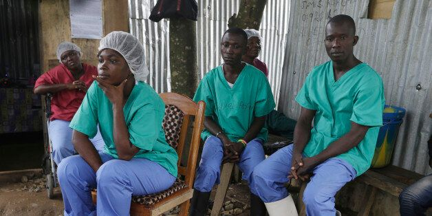 In this Monday, Aug. 10, 2015 photo, health workers take a break at the Kenema Government Hospital, where...