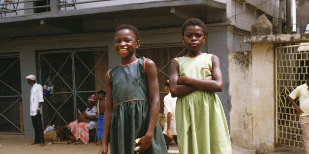 Two young girls pose for the camera along Fourah Bay Road in Freetown, Sierra Leone, March 1985 (Photo...