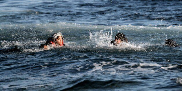 Refugees and migrants swim as they try to reach the shore of the Greek Lesbos island after crossing the...