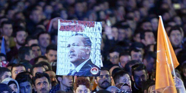 Supporters of the Justice and Development Party (AKP) hold a banner of Turkish President Recep Tayyip...