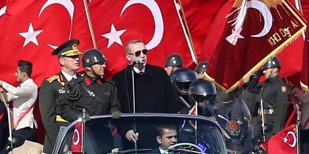 Turkish President Recep Tayyip Erdogan (R) speaks through a microphone next to Chief of the General Staff...