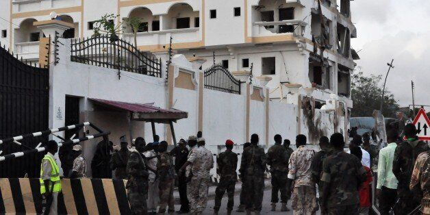Somali soldiers stand in front of the damaged Jazeera Palace hotel following a suicide attack in Mogadishu...