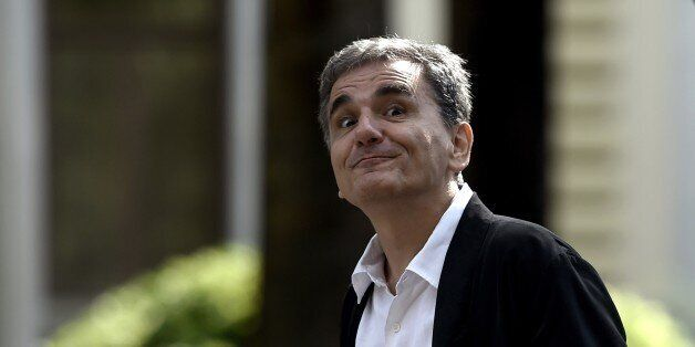 Greek Finance Minister Euclides Tsakalotos grimaces as he leaves the presidential palace after the swearing-in...