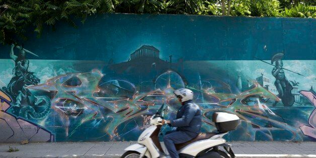 A rider drives his scooter past graffiti in Athens on Thursday, June 4, 2015. High-ranking members of...
