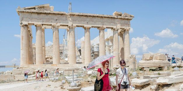 Tourists walk trough the ancient Acropolis hill, with the ruins of the fifth century BC Parthenon temple...