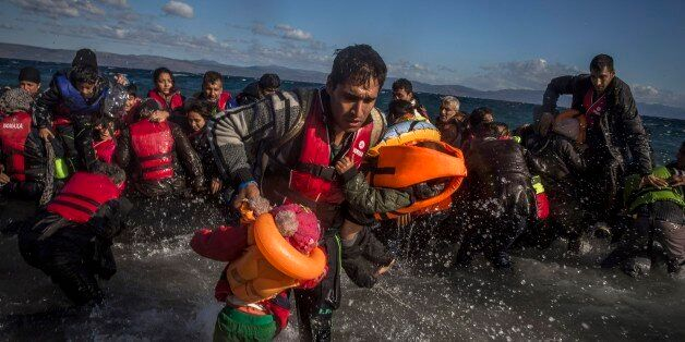 Afghan migrants disembark safely from their frail boat in bad weather on the Greek island of Lesbos after...
