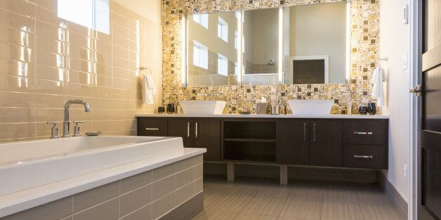 Luxurious modern home bathroom with tiled floor, walls and soaking