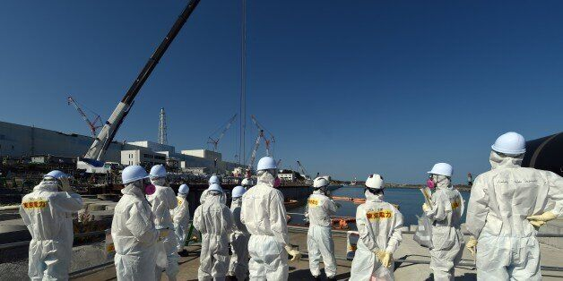 Journalists watch power plant workers install a seaside impermeable wall at the Fukushima Daiichi nuclear...