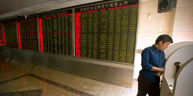 A Chinese investor uses a computer terminal to monitor stock prices at a brokerage house in Beijing,...