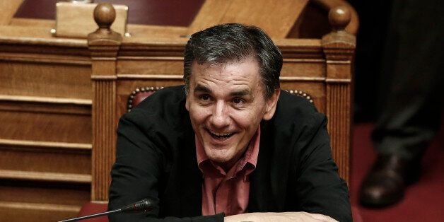 Greece's Finance Minister Euclid Tsakalotos smiles during a parliament vote on a new austerity reform...