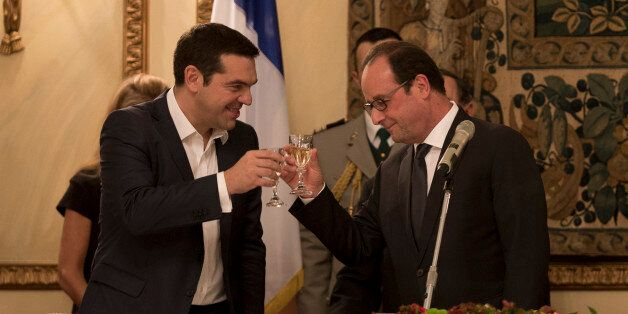 French President Francois Hollande, right and Greek Prime Minister Alexis Tsipras raise their glasses...