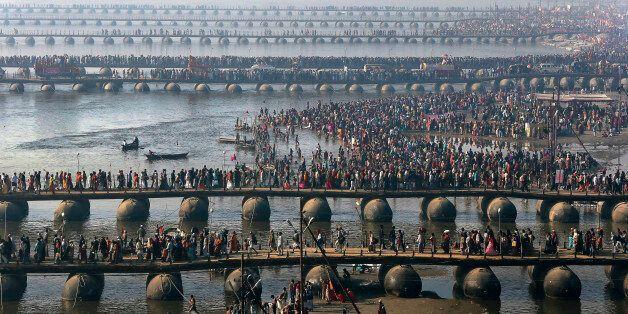 FILE - In this Feb. 10, 2013 file photo, Hindu devotees walk across pontoon bridges to take a holy dip...