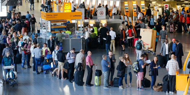 Passengers queue in front of the counters in a terminal at the airport as Lufthansa pilots went on a...