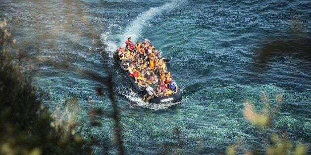 LESBOS ISLAND, GREECE - SEPTEMBER 19: Refugees on a rubber boat reach the shore of Eftalou beach, north...