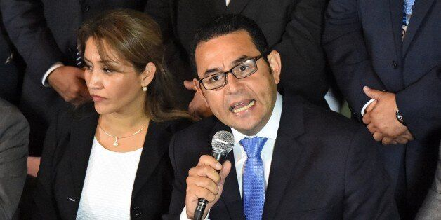 President-elect Jimmy Morales, of the National Front Convergence, delivers a speech next to his wife...