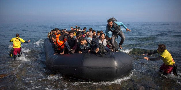 Migrants and refugees arrive on a dinghy from the Turkish coast to the northeastern Greek island of Lesbos,...