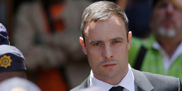 FILE - In this Friday, Oct. 17, 2014 file photo, Oscar Pistorius is escorted by police officers as he...