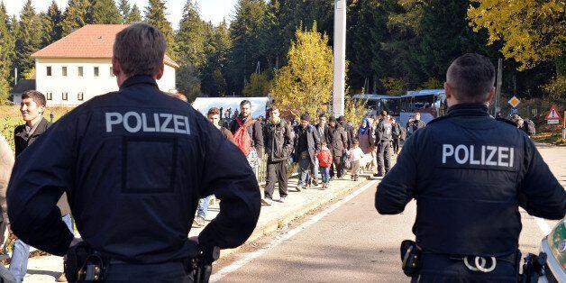 German police officers watch migrants crossing the border between Austria and Germany in Wegscheid near...