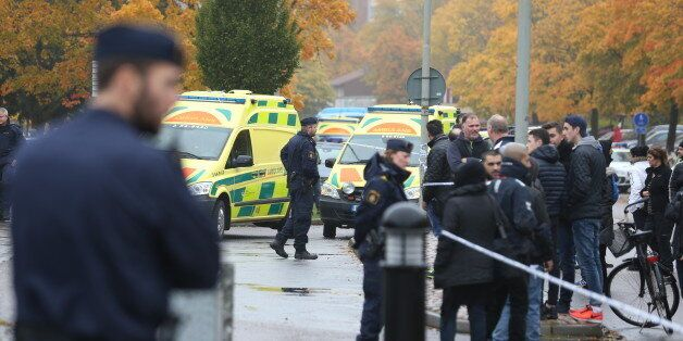 A crowd gathers outside, as emergency services attend the scene of a sword attack by a masked man at...