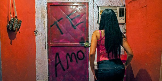 A prostitute who uses the alias 'Elena' sits in her room at the Blue House brothel in Puerto Cabello,...