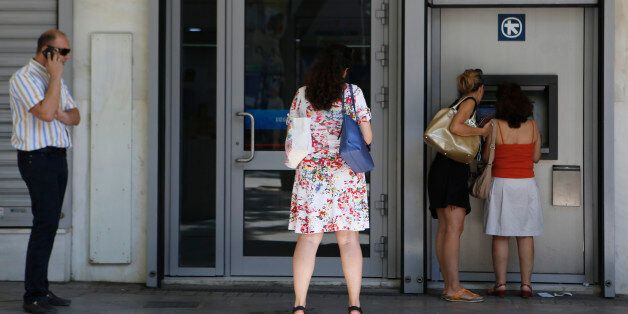 The women right use the ATM machine as two other people wait outside of a closed bank in central Athens,...