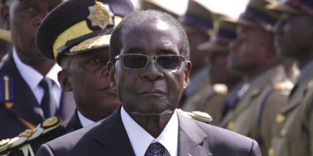 FILE - In this Thursday, May 14, 2015 file photo, Zimbabwean President Robert Mugabe, centre, officiates...