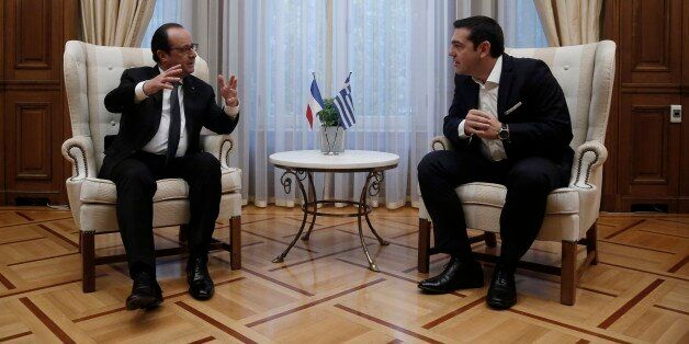 French President Francois Hollande, left, talks with the Greek Prime Minister Alexis Tsipras during their...