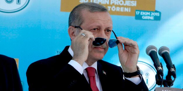 Turkish President Recep Tayyip Erdogan adjust his sunglasses before making a speech to his supporters,...