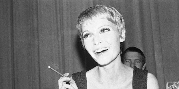 Cigar-smoking Mia Farrow, wife of American singer Frank Sinatra, is shown in her hotel room in Berlin, during a news conference, April 20, 1967. She will star in the movie