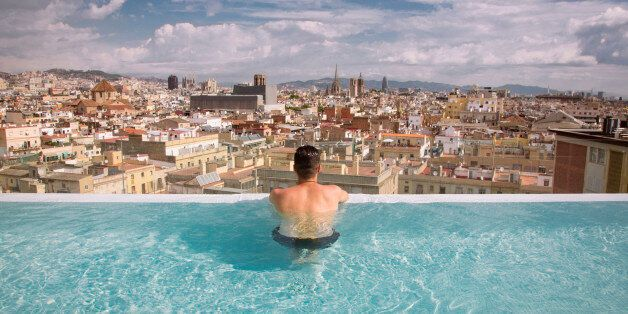 Picture of the young guy taken from the back overlooking Barcelona, taken in the pool on the top floor of the luxury hotel.