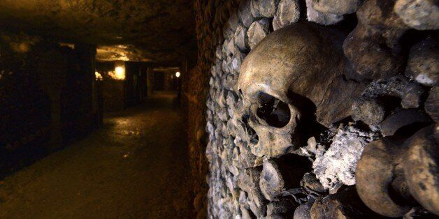 Photo taken on August 7, 2014 at the Catacombs of Paris shows skulls and bones stacked and arranged....