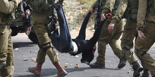 Israeli soldiers carry a wounded Palestinian stone thrower who was shot by infiltrated members of the...