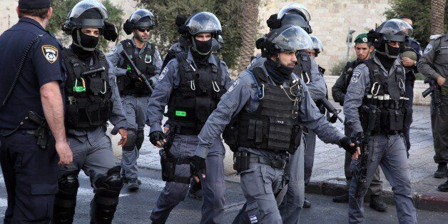 Israeli border guards secure the site after a Palestinian stabbed two police officers before being shot...