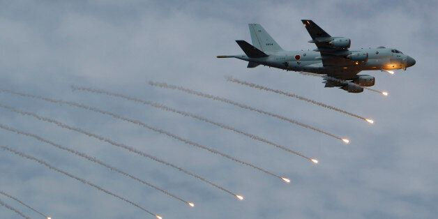 Japan Maritime Self-Defense Force's P-1 patrol plane fires flares during an event held ahead of Sunday's...