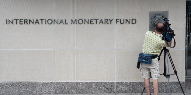 A televison camerman films the logo of the International Monetary Fund (IMF) at the organization's headquarters...