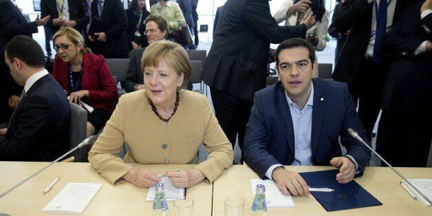 German chancellor Angela Merkel (L) talks with Greek prime minister Alexis Tsipras at the begining of...