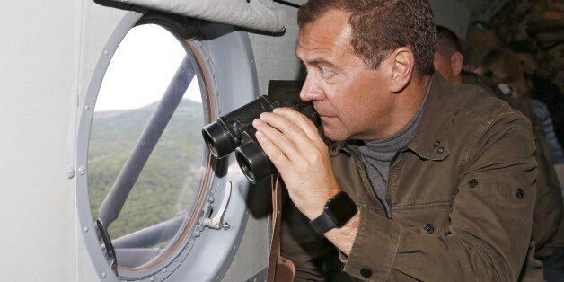In this photo taken on Saturday, Aug. 22, 2015, Russian Prime Minister Dmitry Medvedev holds a binoculars...