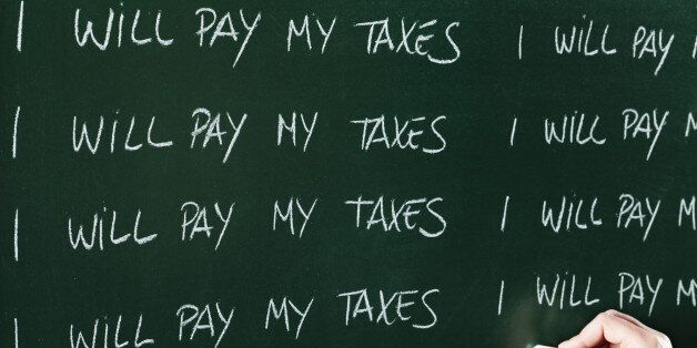 I will pay my taxes sentence written repeatedly on blackboard as a punishment. Focus is on the text block...