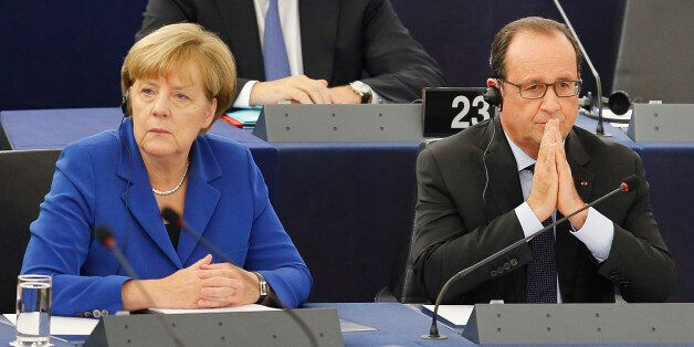 German Chancellor Angela Merkel, left, is seated next to French President Francois Hollande before addressing...