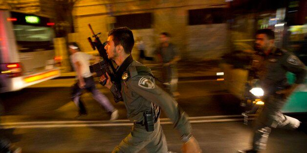 Israeli policemen run looking for a possible stabbing suspect in Jerusalem, Wednesday, Oct. 14, 2015....