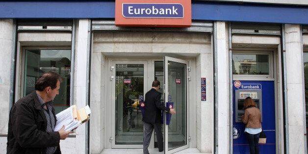 Customers use the ATM and enter a branch of Eurobank in central Athens, Tuesday, April 23, 2013. Greece's...