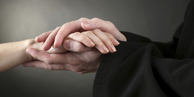 Priest holding woman hands, on green