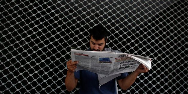A demonstrator reads a newspaper outside the Greek finance ministry during a protest by the Communist...