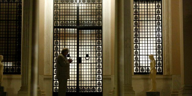 Greek State Minister Alekos Flampouraris uses his mobile phone outside of the gate of Maximos Mansion...