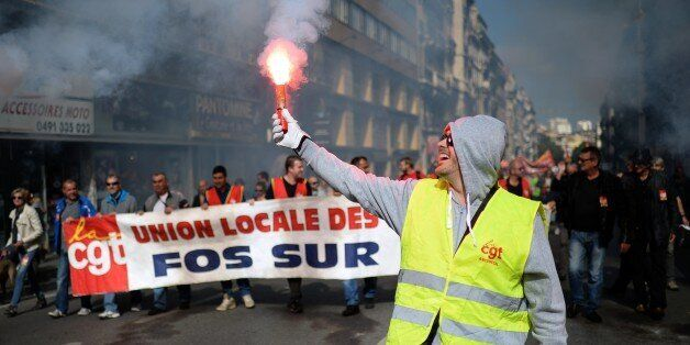 A demonstrator holds a smoke projectile during a National Action Day organised by French labour unions...