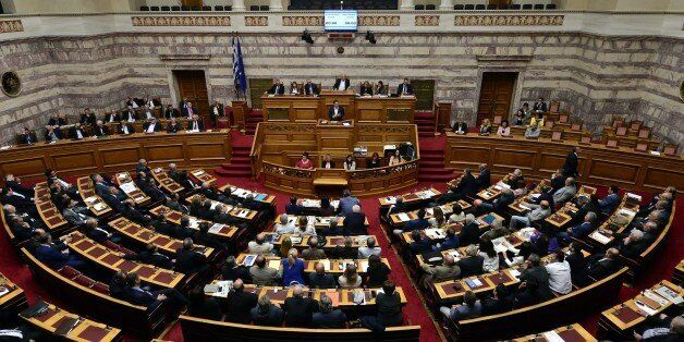 Greek Prime Minister Alexis Tsipras (C) addresses lawmakers during a parliament session prior the confidence...