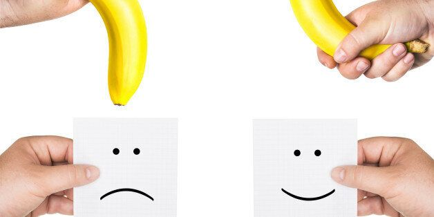 concept of potency, the concept of penis,  two men's hands holding smiley and sad  faces,  two hands hold the big bananas up and down, like the man penis, short, small, medium, average, long size