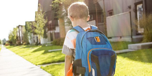 A young boy walking and carrying his skateboard and backpack on his way to